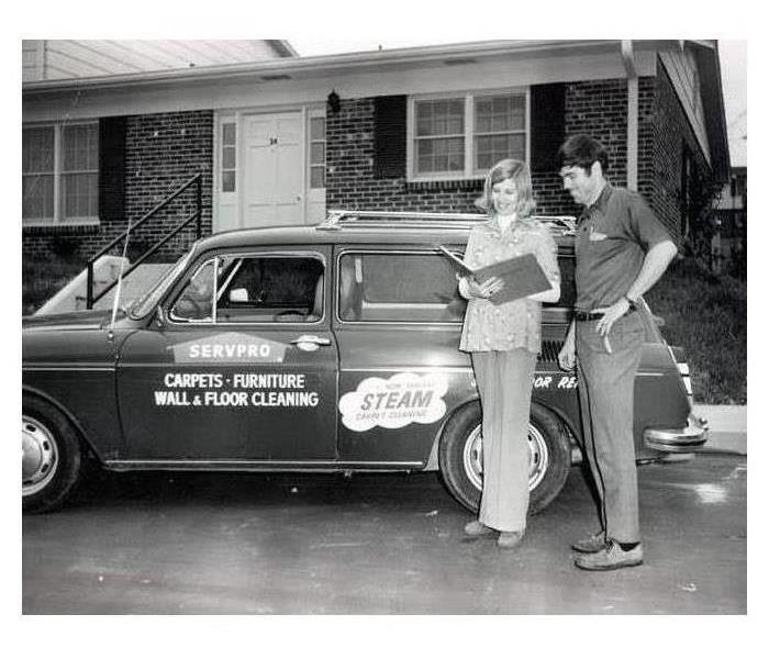 Servpro industries owners standing in front of their Servpro station wagon in 1967